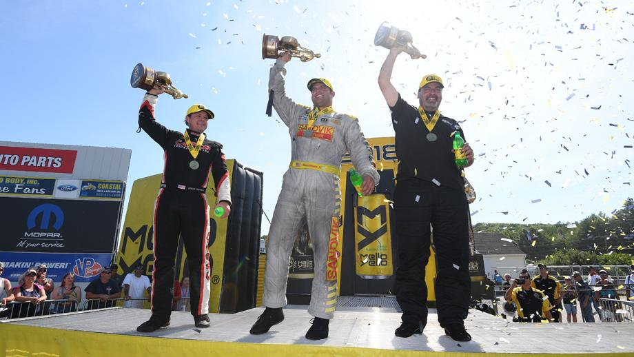The NHRA New England Nationals winners lift their Wallys on stage.