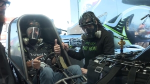Iron Maiden drummer Nicko McBrain warms up Alexis DeJoira's Funny car